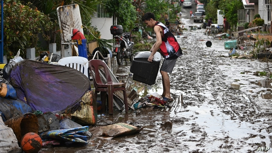 Residents clean their homes following flooding in Batangas City, south of Manila, Nov. 2, 2020, after Super Typhoon Goni made landfall in the Philippines.