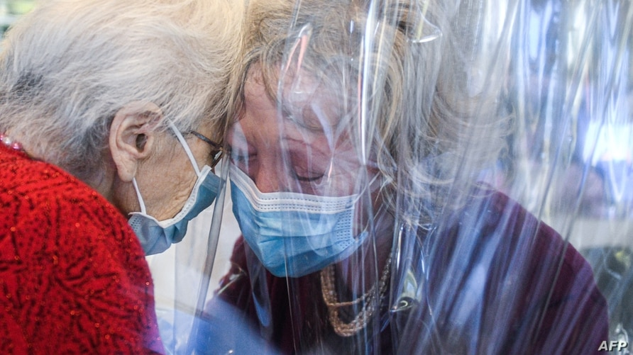 "A resident (L) of the Domenico Sartor nursing home in Castelfranco Veneto, near Venice, Italy, hugs her visiting daughter through a plastic screen in a so-called ""Hug Room"" amid the COVID-19 pandemic."