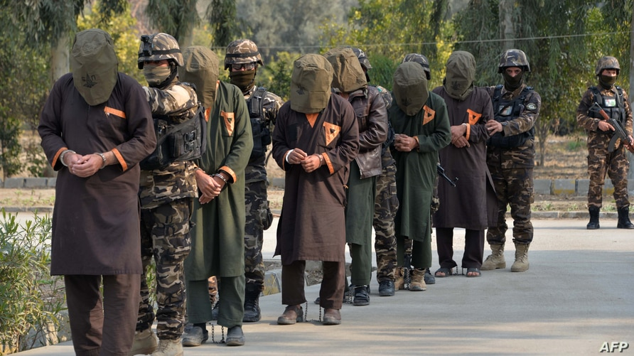 FILE - Forces with Afghanistan's National Directorate Security (NDS) escort alleged Taliban fighters after they are presented to the media, in Jalalabad, Afghanistan, Jan. 23, 2019.