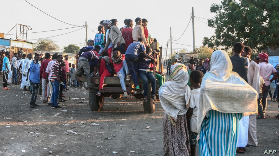 People fleeing intense fighting in Ethiopia's Tigray region gather in the bordering Sudanese village 8, east of the town of Gadaref, Nov. 13, 2020.