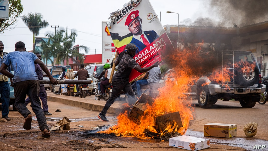 A supporter of Ugandan musician-turned-politician Robert Kyagulanyi, also known as Bobi Wine, carries his poster during a protest against the arrest of Kyagulanyi, during his campaign rally in Kampala, Uganda, Nov. 18, 2020.