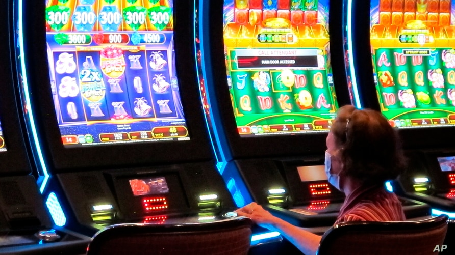 A woman plays a slot machine at the Golden Nugget casino in Atlantic City, New Jersey, July 2, 2020.