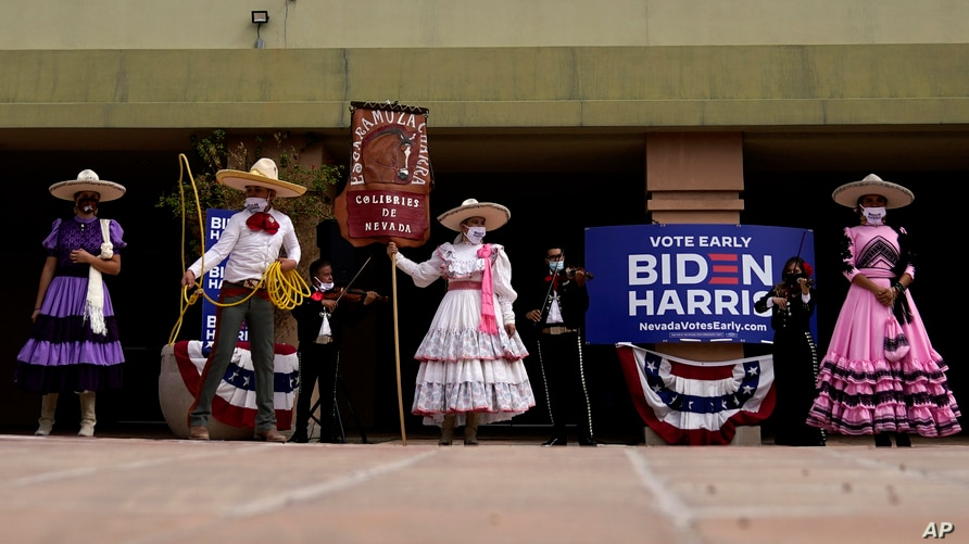 FILE - Members of the Latino community hold signs as former vice president and then-Democratic presidential candidate Joe Biden meets with Latino leaders at East Las Vegas Community Center, in Las Vegas, Nevada, Oct. 9, 2020.
