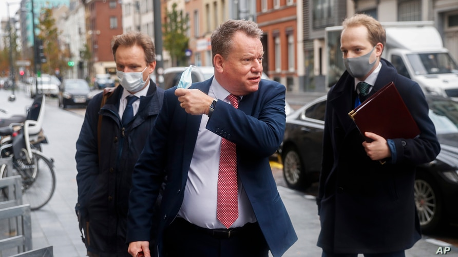 Britain's chief negotiator David Frost, center, removes his face mask to talk to the media as he arrives for Brexit talks with EU chief negotiator Michel Barnier in Brussels, Belgium, Nov. 16, 2020.