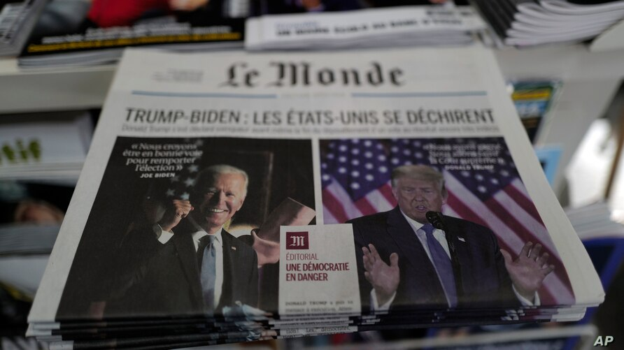 "Copies of the French newspaper Le Monde with the headline ""Trump-Biden: the United States is tearing itself apart"" is seen at a newspaper stand in Paris, France, Nov. 4, 2020."