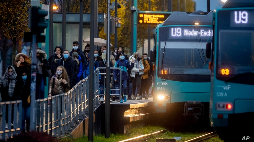 People wearing face masks arrive at a subway station in Frankfurt, Germany, Nov. 19, 2020.