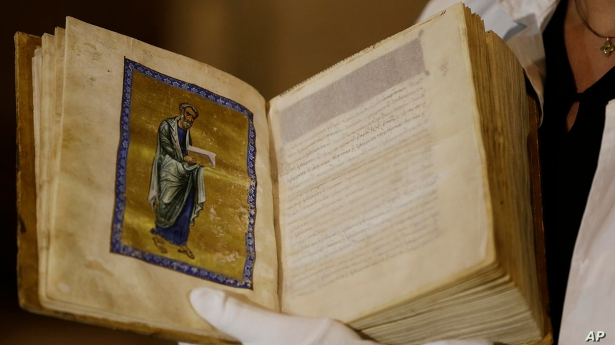 FILE - A Greek conservator holds up a repatriated 12th Century illuminated manuscript bible, during its presentation at the Byzantine Museum in Athens, Sept. 15, 2014.