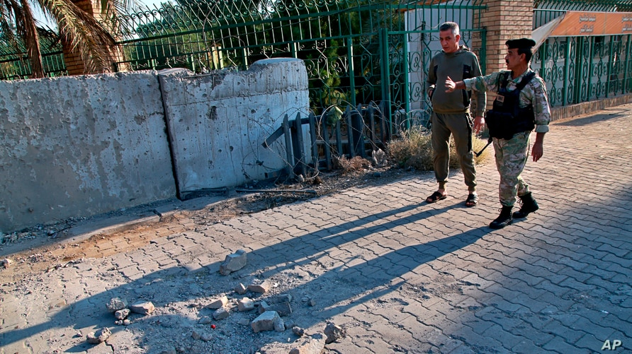 Security forces inspect the scene of a rocket attack at the gate of al-Zawra public park in Baghdad, Iraq, Nov. 18, 2020. Rockets struck Iraq's capital on Tuesday with four landing inside its heavily fortified Green Zone.