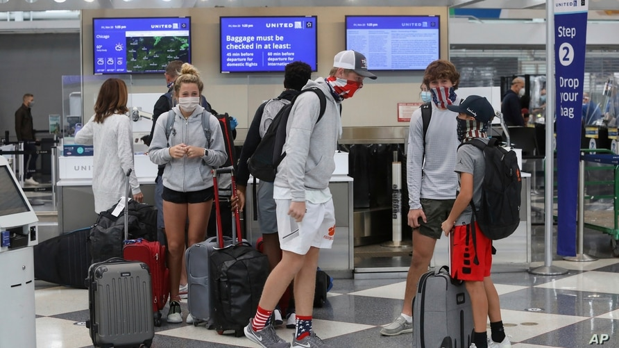 Travelers wearing maskes talk in a terminal at O'Hare International Airport, in Chicago, Illinois, Nov. 20, 2020.