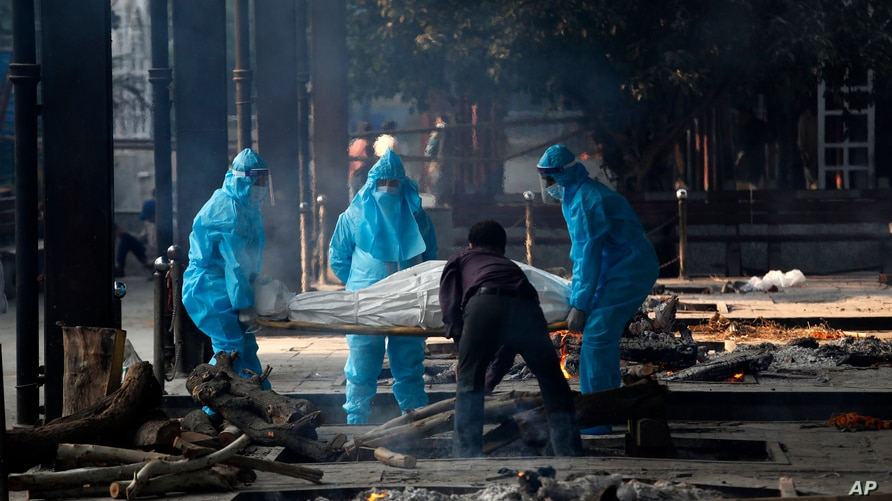 Health workers in personal protective equipment carry the body of a COVID-19 victim for cremation in New Delhi, India, Nov. 19, 2020.