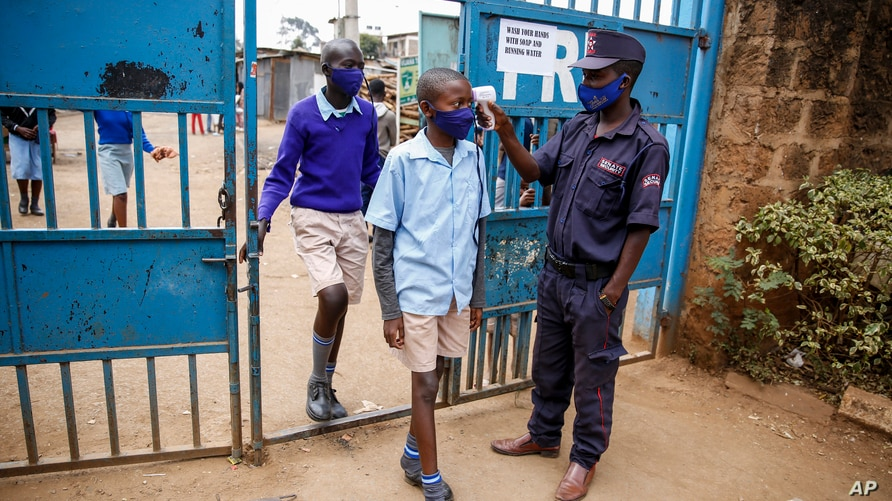 Schoolchildren have their temperature taken as they arrive at the Olympic Primary School in Kibera, one of the capital Nairobi's poorest areas in Kenya, Oct. 12, 2020.