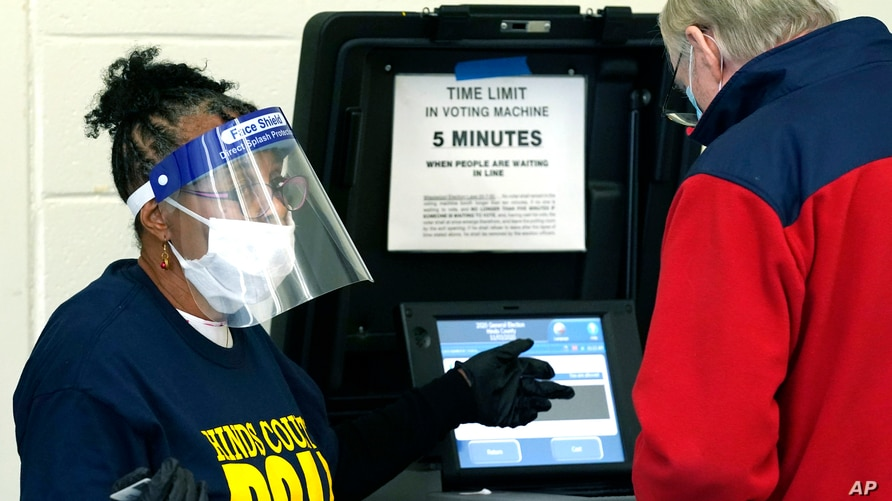 Precinct 36 poll worker Vivian Bibens in her personal protective equipment explains the purpose of the ballot scanner to a voter on Election Day in Jackson, Miss., Nov. 3, 2020.