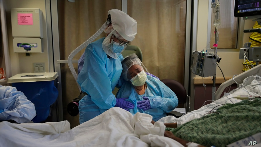 FILE - A woman, center, is comforted by a nurse, left, as she weeps while sitting at the bedside of her dying husband, in St. Jude Medical Center's COVID-19 unit in Fullerton, California, July 31, 2020.
