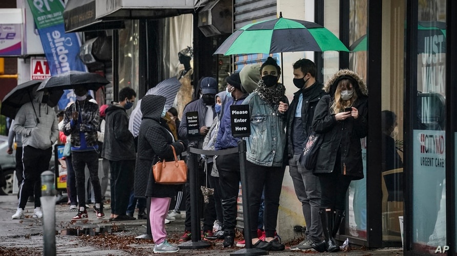 People queue outside an urgent care clinic, a designated COVID-19 testing center, in New York City, in Nov. 13, 2020.
