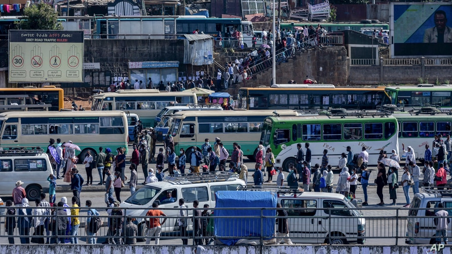 Passengers queue to get on buses in Ethiopia's capital Addis Ababa, Nov. 6, 2020, as the government carried out airstrikes in the country's restive Tigray region, prompting Sudan to close part of its border with Ethiopia.