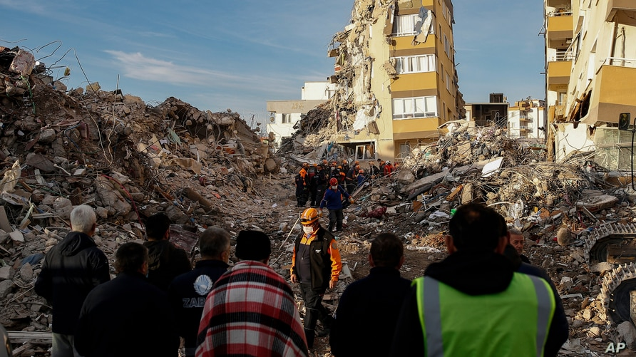 Local residents watch as members of rescue services work at collapsed buildings, destroyed in the Oct. 30 earthquake in Izmir, Turkey, Nov. 3, 2020.