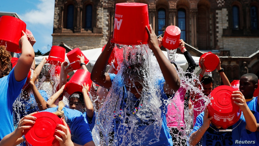 "FILE - People pour buckets of ice water over her heads as part of the ""ALS Ice Bucket Challenge,"" a viral activity started by Pat Quinn and Pete Frates to raise money for research into the ALS disease, in Boston, Massachusetts, July 15, 2019."