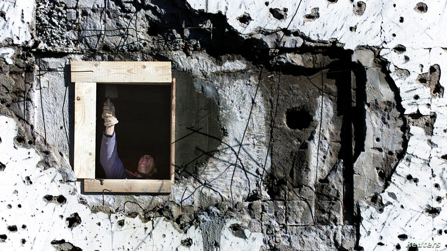 FILE - A worker repairs a war-shattered building at the former front line between two Bosnian entities in Sarajevo's suburb of Dobrinja, Nov. 20, 2000.