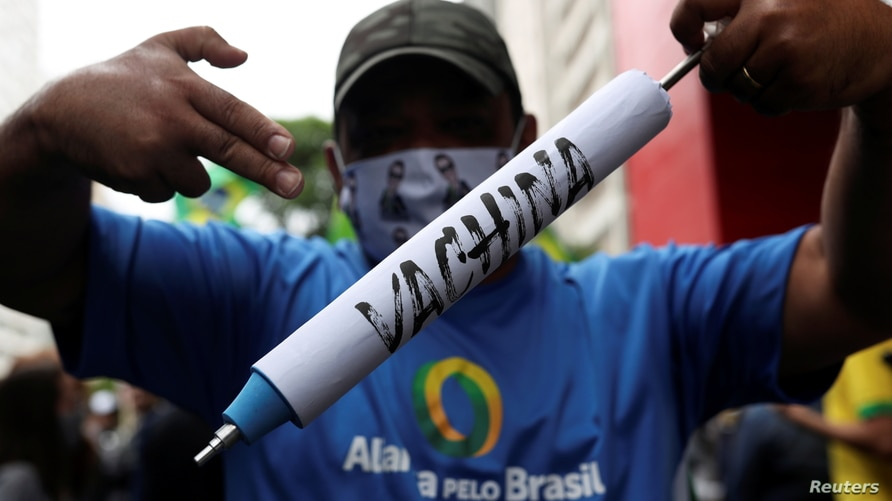 FILE - A man holds a mock syringe as demonstrators protest against Sao Paulo state governor Joao Doria and China's Sinovac COVID-19 vaccine, in Sao Paulo, Brazil, Nov. 1, 2020.