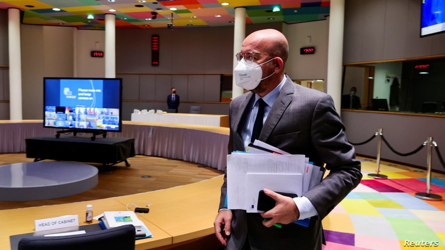 FILE - European Council President Charles Michel, wearing a protective mask, arrives for an EU Summit video conference, at the European Council building in Brussels, Belgium, Nov. 19, 2020.
