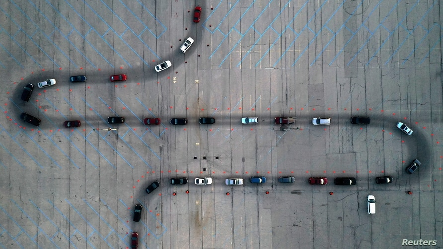 An aerial view shows vehicles waiting at a drive-thru COVID-19 testing site in a parking lot in Milwaukee, Wisconsin, Nov. 5, 2020.