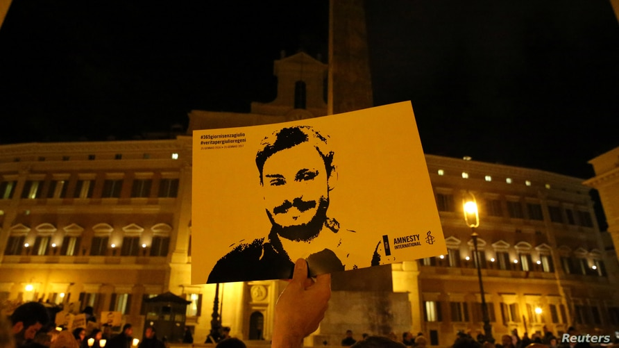 FILE - A man holds a placard during a vigil in memory of Giulio Regeni, who was found murdered in Cairo, Egypt, in January of 2016, in downtown Rome, Italy, Jan. 25, 2017.