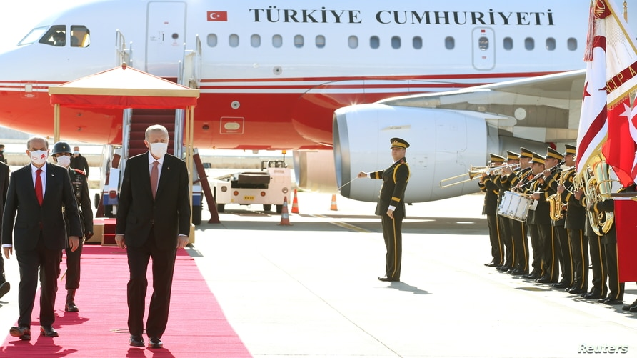 Turkish President Tayyip Erdogan reviews a guard of honor with Turkish Cypriot leader Ersin Tatar upon his arrival in northern Nicosia, Cyprus, Nov. 15, 2020.