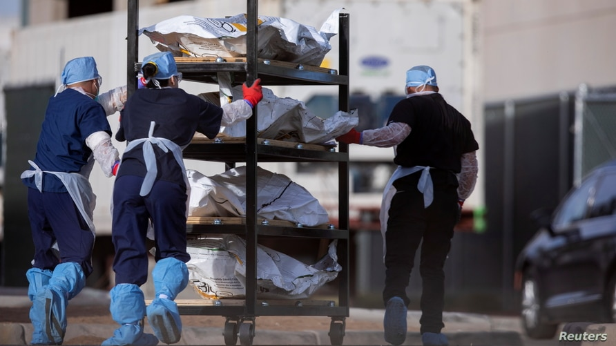"El Paso County Medical Examiner's Office staff roll bodies that are in bags labeled ""Covid"" from refrigerated trailers into the morgue office amid the COVID-19 outbreak, in El Paso, Texas, Nov. 23, 2020."