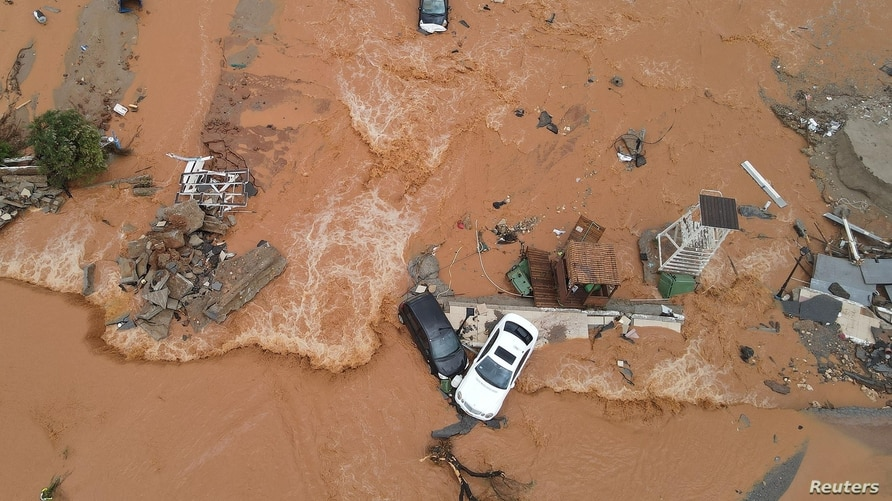 Debris and damaged cars are seen on a flooded seaside road during heavy rainfall at the village of Gournes on the island of Crete, Greece, Nov. 10, 2020.