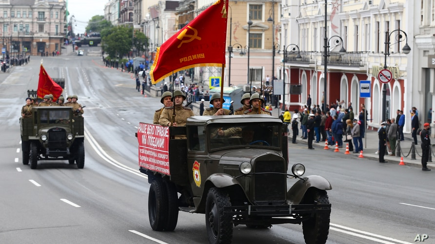 Participants wearing historical uniforms ride in the back of a WWII-era truck during a military parade, which marks the 75th…
