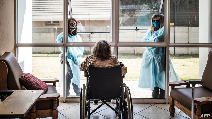 Relatives chat through a window to a wheelchair bound woman, a resident of Casa Serena, an Old Age home in Johannesburg, on…