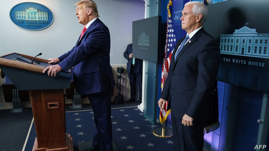 US President Donald Trump with Vice President Mike Pence (R), delivers remarks on the stock market during an unscheduled…