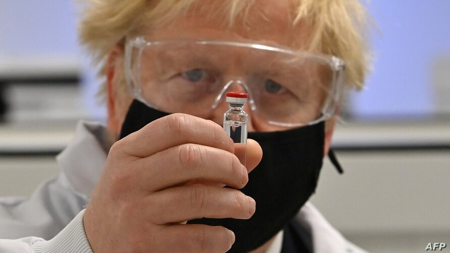 Britain's Prime Minister Boris Johnson poses for a photograph with a vial of the AstraZeneca/Oxford University COVID-19…