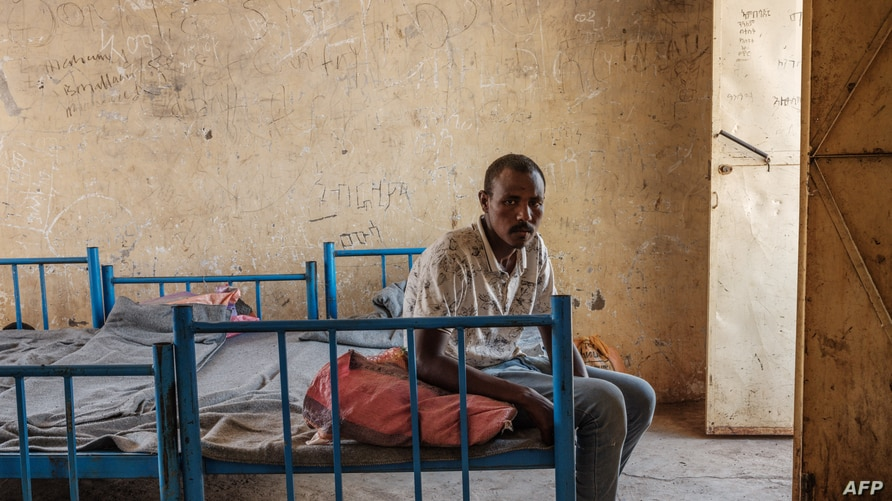 Kheder Adam, an Eritrean refugee who fled Ethiopia's Tigray conflict, poses on his bed after an interview with AFP at the…