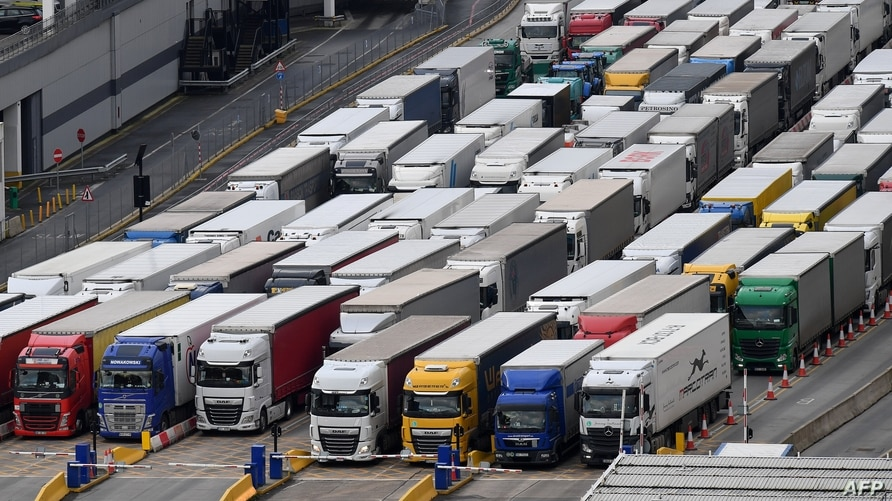 Freight lorries are seen queueing as they wait to enter the port of Dover on the south coast of England on December 10, 2020,…