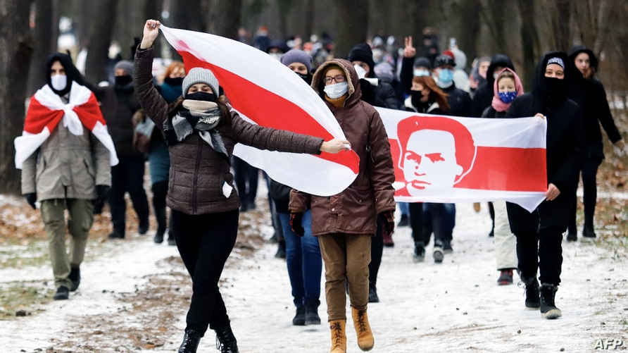 Opposition supporters carrying former white-red-white flags of Belarus parade through the streets during a rally against the…