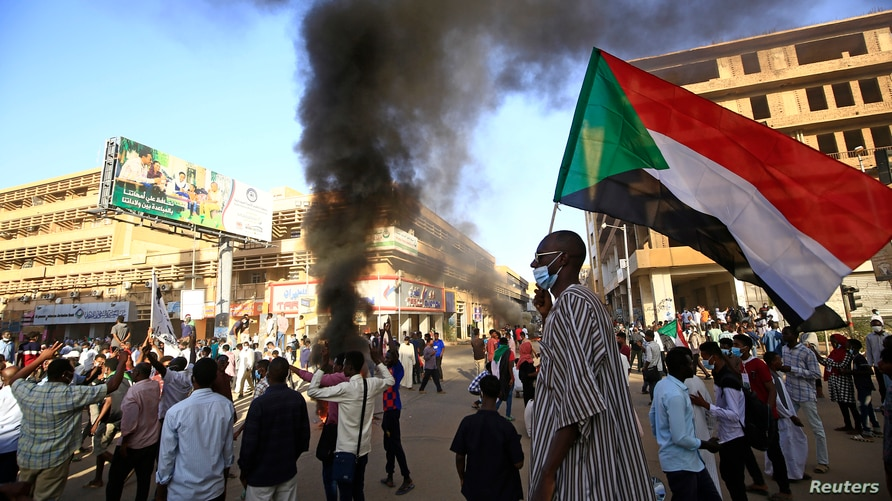 A Sudanese man wearing a face mask waves his country's national flag during protests in the capital Khartoum to mark the second…