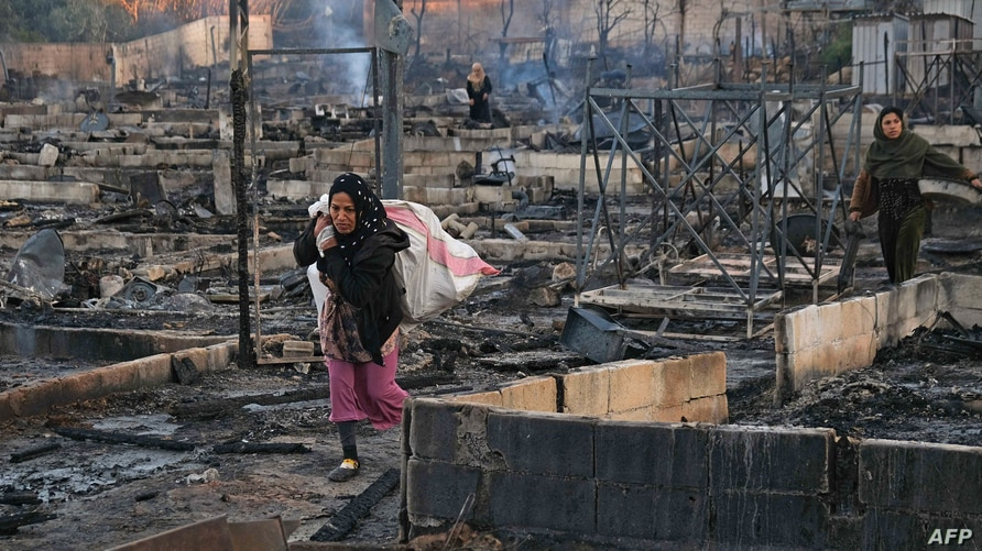 Syrian refugees salvage belongings from the wreckage of their shelters at a camp set on fire overnight in the northern Lebanese…