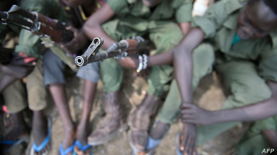 Young boys, children soldiers sit on February 10, 2015 with their rifles at a ceremony of the child soldiers disarmament,…