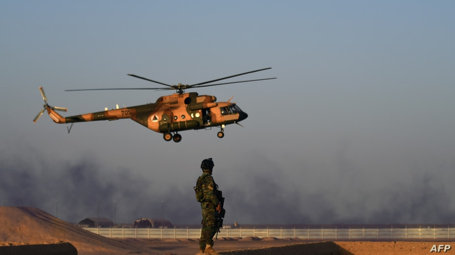 In this photograph taken on August 27, 2017 an Afghan Commandos stands guard while an Afghan Air Force helicopter flies past…