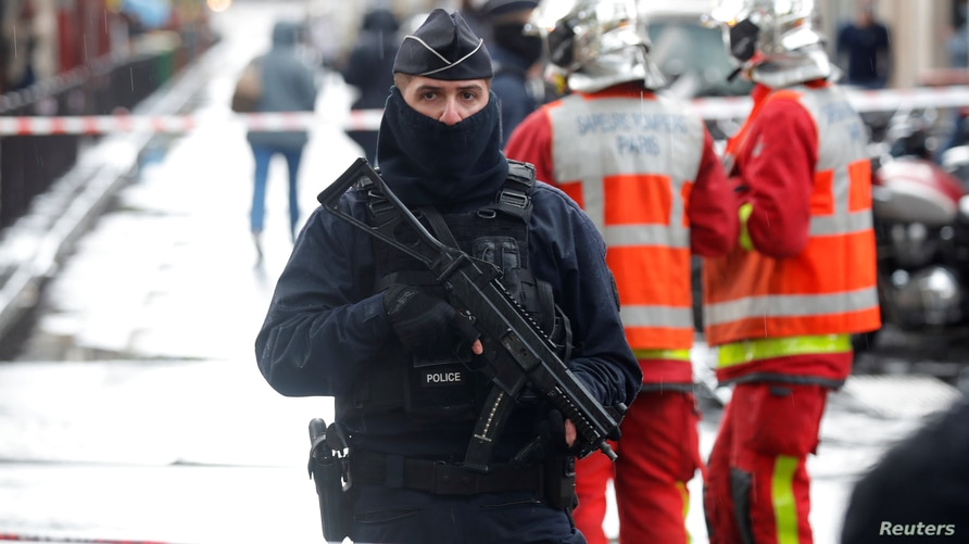 A police officer stands guard at the scene of an incident near the former offices of French magazine Charlie Hebdo, in Paris,…