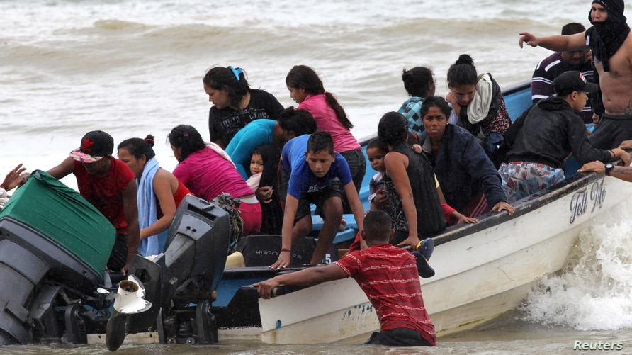 Venezuelan migrants, who were recently deported, arrive at shore on Los Iros Beach after their return to the island, in Erin,…