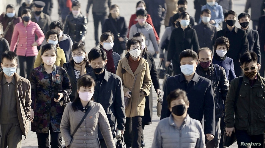 People wearing protective face masks commute amid concerns over the new coronavirus disease (COVID-19) in Pyongyang, North…