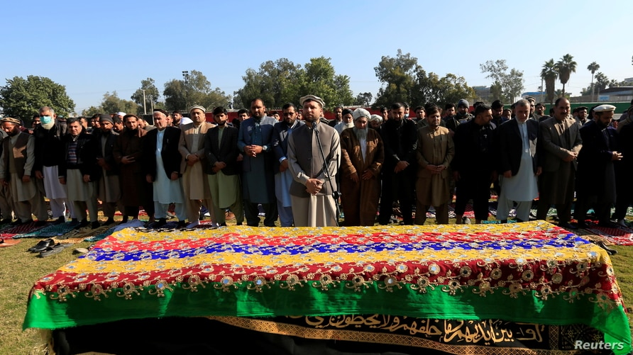 Afghan men pray near the coffin of journalist Malalai Maiwand, who was shot and killed by unknown gunmen in Jalalabad,…