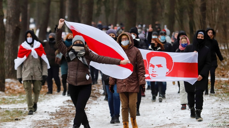 Opposition supporters carry historical white-red-white flags of Belarus as they attend a rally to reject the presidential…