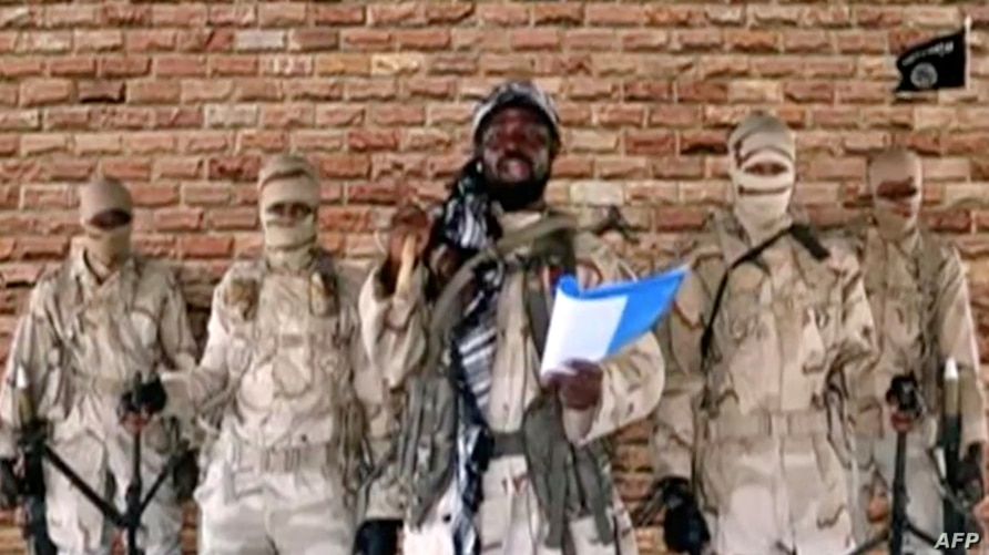 FILE PHOTO: The leader of one of the Boko Haram group's factions, Abubakar Shekau speaks in front of guards in an unknown…