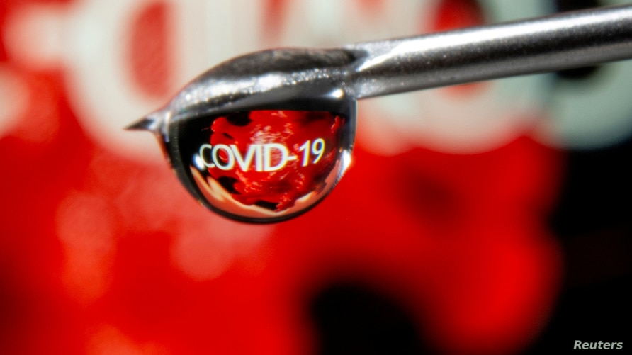 """FILE PHOTO: The word """"COVID-19"""" is reflected in a drop on a syringe needle in this illustration taken November 9, 2020. REUTERS…"""