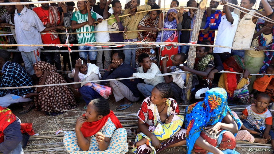 FILE PHOTO: Ethiopians who fled the ongoing fighting in Tigray region gather to receive relief aid at the Um-Rakoba camp on the…