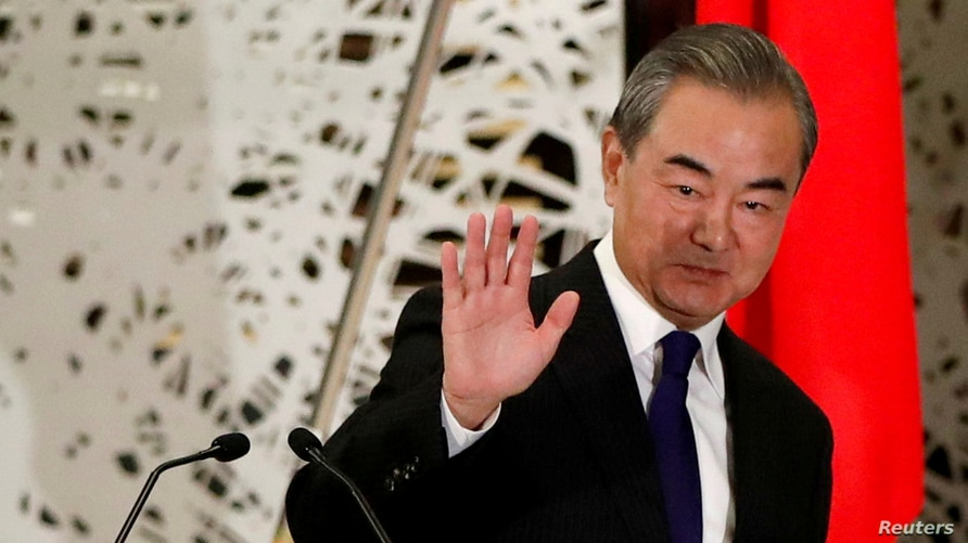 FILE PHOTO: China's State Councillor and Foreign Minister Wang Yi waves as he leaves a news conference in Tokyo, Japan,…
