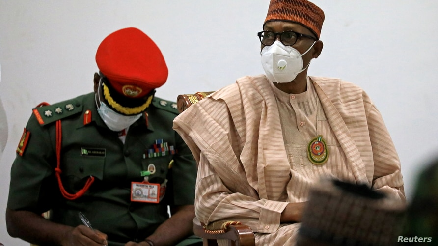 Nigerian President Muhammadu Buhari looks on after security forces rescued schoolboys at the Government house in Katsina,…